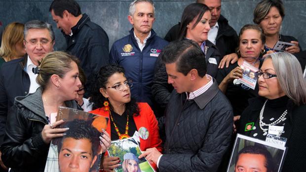 El presidente Enrique Peña Nieto con familiares de desaparecidos, el pasado mes de octubre tras aprobarse la Ley de Desaparicón Forzada. A la derecha, Yolanda Morán con la foto de su hijo Dan Jeremeel