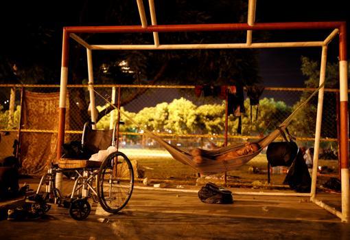 Un hombre duerme en un centro deportivo que acoge a numerosos venezolanos