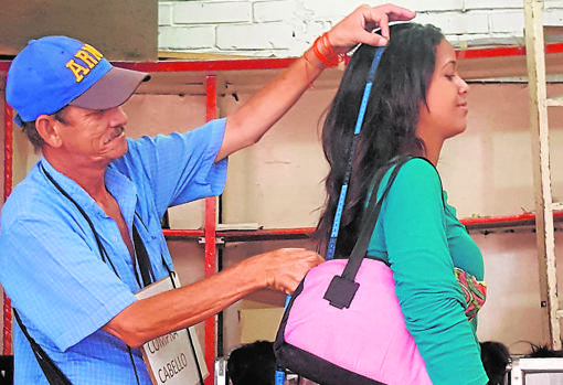 Karelis Nieves, mientras miden la longitud de su melena para venderla