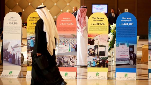 Participantes pasan delante de unos carteles en la Conferencia Internacional de Kuwait para recoger fondos para la reconstrucción de Irak