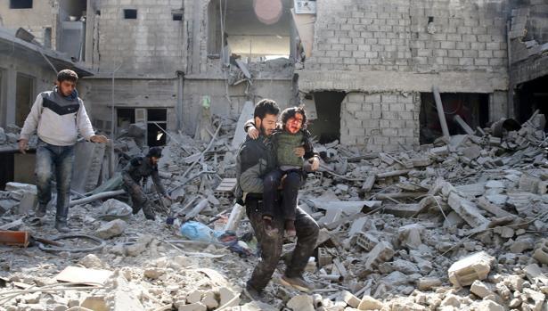 Un hombre lleva en brazos a un chico sobre los escombros de un edificio en Guta, en Siria