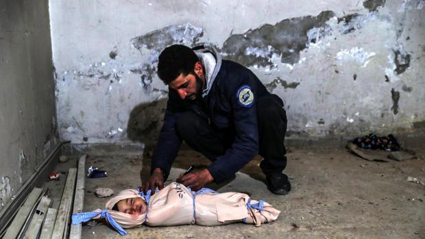 Un voluntario de los cascos blancos escribe información en el cuerpo sin vida de un niño muerto tras un bombardeo en Guta Oriental