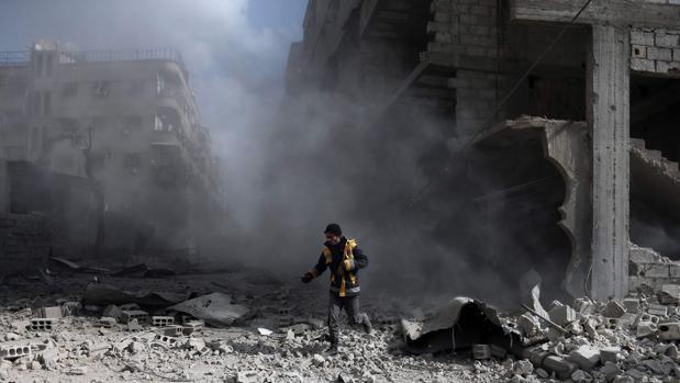 Un voluntario corre entre los escombros de edificios bombardeados en Guta oriental