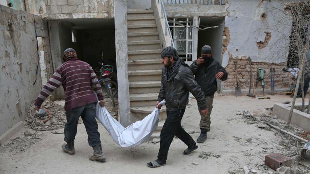 Miembros de la defensa civil retiran el cuerpo de un fallecido en un bombardeo en Haza