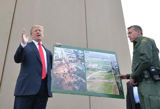 Trump sostiene una foto del antes y el después de la frontera de San Diegp con México