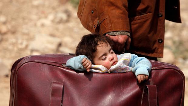 Un niño es conducido por un familiar en una maleta, ayer en Beit Sawa, al este de Guta