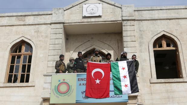 Miembros de las fuerzas turcas y del Ejército Sirio Libre posan con las banderas desplegadas en Afrín
