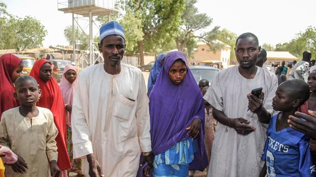 Una de las niñas liberadas por Boko Haram camina junto a su padre en la localidad de Dapchi, donde fue secuestrada en febrero