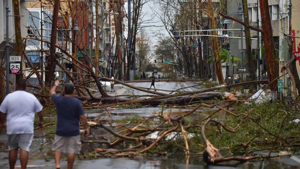 Dos hombres caminan por las calles de Puerto Rico después del paso del huracán María