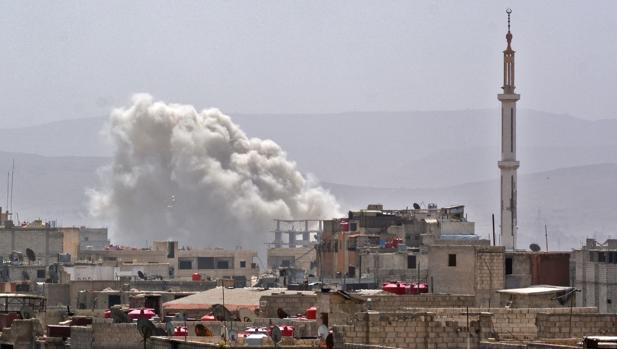Columna de humo en el sur de la capital siria, Damasco, dende las fuerzas de Al Assad han bombardeado un enclave en manos de los rebeldes