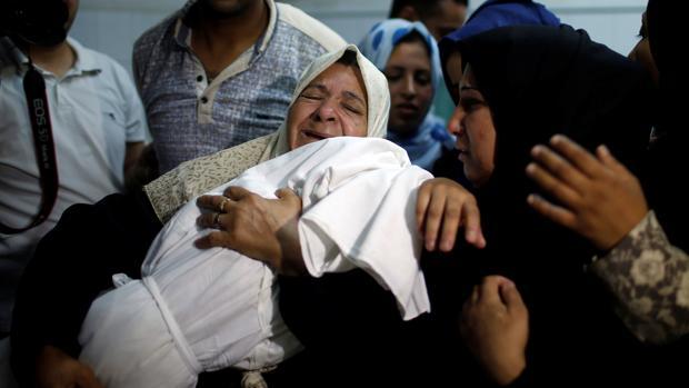 Familiares del bebé de ocho meses abrazan el cuerpo del niño