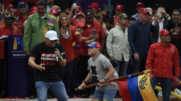 Maradona porta la bandera de Venezuela mientras baila ante los ojos del presidente de Maduro en el cierre de campaña