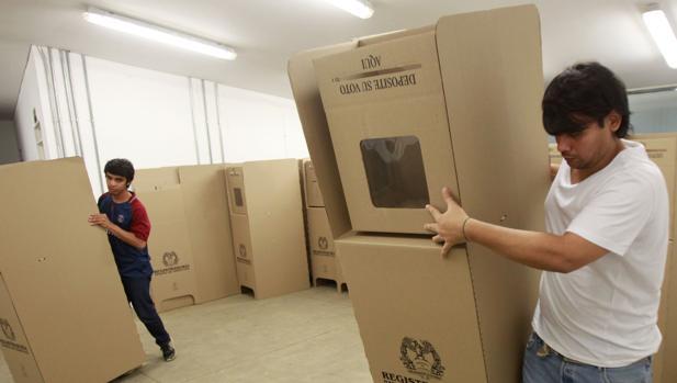 Funcionarios de la Registraduría Nacional de Colombia instalan mesas de votación en un puesto electoral