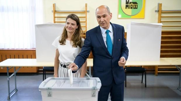 El ex primer ministro esloveno Janez Jansa vota, acompañado de su esposa