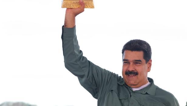 Fotografía cedida por prensa de Miraflores donde se observa al mandatario venezolano, Nicolás Maduro, quien sostiene un lingote de oro, durante un acto de Gobierno