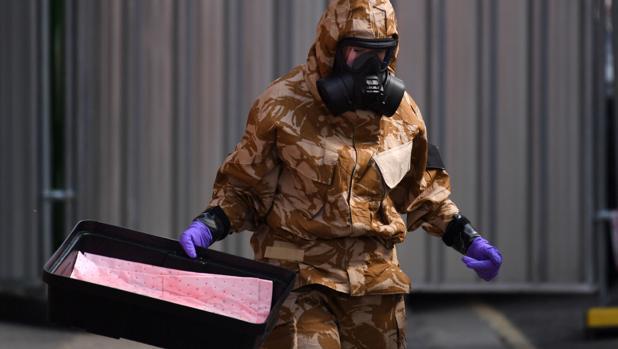 Un investigador que lleva un traje de protección camuflado, guantes y una máscara de gas trabaja en el caso