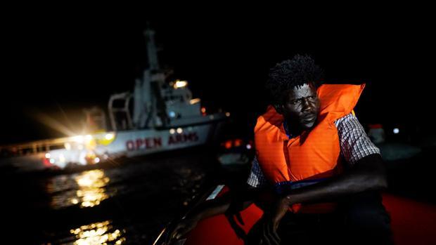 Un migrante se sienta a bordo del barco de rescate de la ONG Proactiva Open Arms en el mar Mediterráneo central