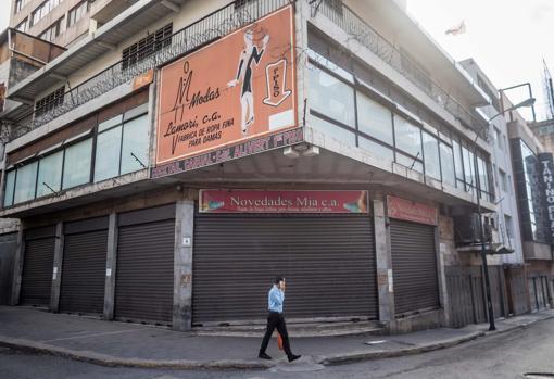 Un hombre camina frente a locales comerciales cerrados