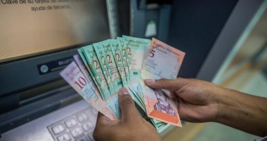 Una persona cuenta dinero del nuevo cono monetario retirado de un cajero automático