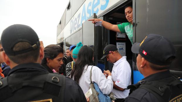 Inmigrantes venezolanos presentan sus documentos al subir a un bus que los llevará a Trujillo desde el Centro Binacional de Atención en Frontera (Cebaf) en Tumbes (Perú)