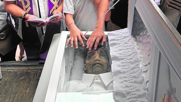 El padre Flavie Villanueva reza un responso junto al cadáver de Roberto Manaligán, abatido en la «guerra sucia» contra las drogas