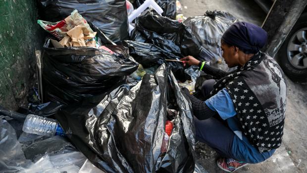 Una mujer mientras hurga en la basura en busca de comida en una calle de Caracas