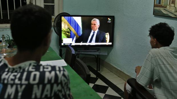 Dos jóvenes ven la entrevista al presidente cubano, Miguel Diaz-Canel, de la cadena de televisión TeleSur
