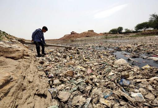 Un niño yemení está rodeado de residuos y desechos, entorno de alto riesgo para el cólera