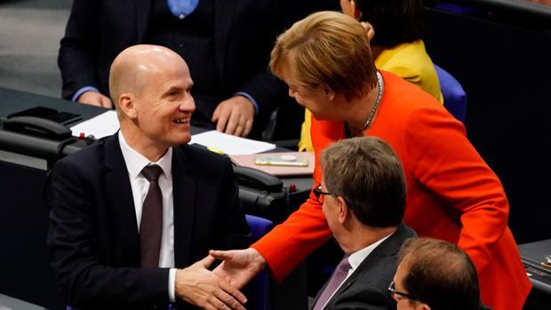 La canciller alemana, Angela Merkel (d), saluda al recién elegido jefe del grupo parlamentario conservador CDU/CSU, Ralph Brinkhaus (i)