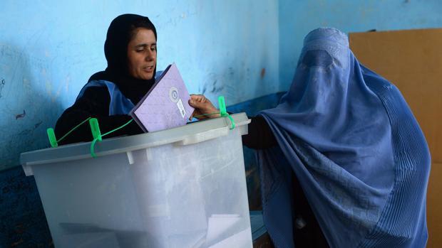 Una mujer vota en un centro electoral afgano