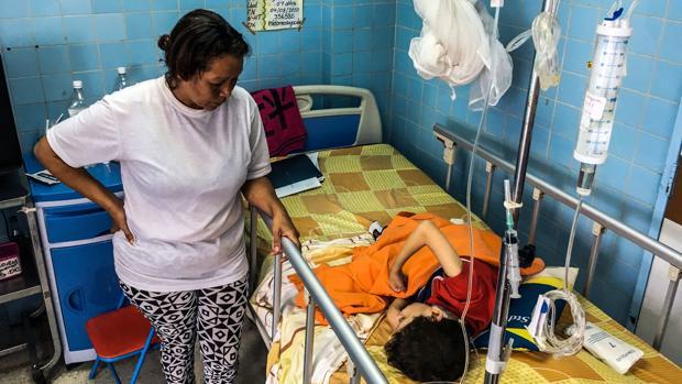 Una mujer está de pie junto a su hijo en la sala de neurocirugía del Hospital de Caracas