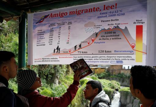 Venezolanos miran una pancarta con información sobre la ruta de Cúcuta a Bucaramanga