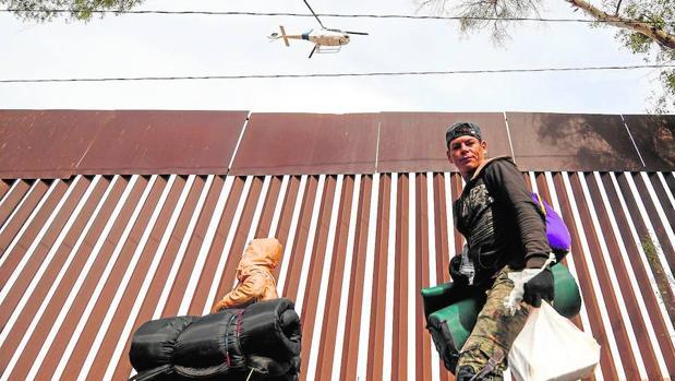 Miembros de la caravana continúan llegando al norte de México. Un helicóptero de la patrulla fronteriza de Estados Unidos sobrevuela la valla fronteriza