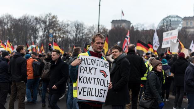 Un manifestante de derecha sostiene un cartel que dice «pacto de migración significa pérdida de control», durante un mitin contra el pacto de migración de la ONU, organizado por el movimiento de derecha Pegida en Berlín