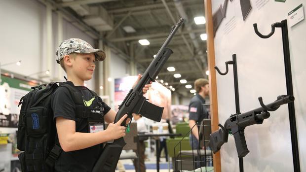 Blaise Maliskey, de 11 años, prueba un arma de fuego en una sala de exhibición en la convención anual de la NRA