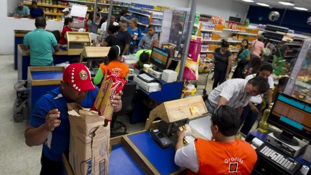 Un grupo de personas hacen las compras dentro de un supermercado en Caracas