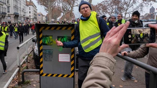 Un chaleco amarillo posa con un radar pintado en Lyon