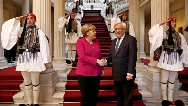 El presidente griego, Prokopis Pavlopoulos (d), recibe a la canciller alemana, Angela Merkel (i), en Atenas (Grecia)