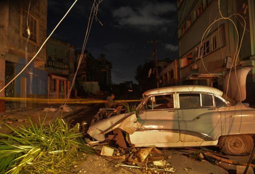 Un coche dañado y postes de electricidad caídos