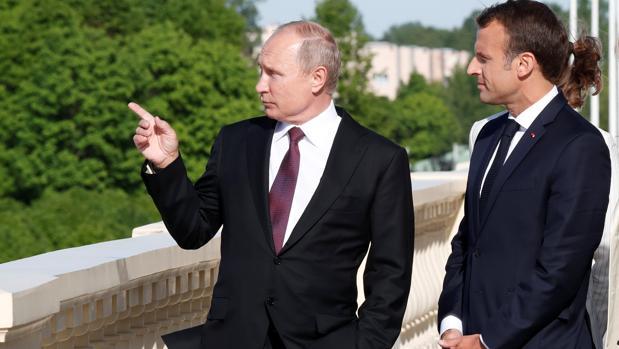 Vladimir Putin y Emmanuel Macron hablan durante una reunión en Rusia