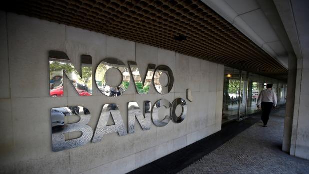 Un hombre camina junto a una sucursal de Novo Banco en Lisboa