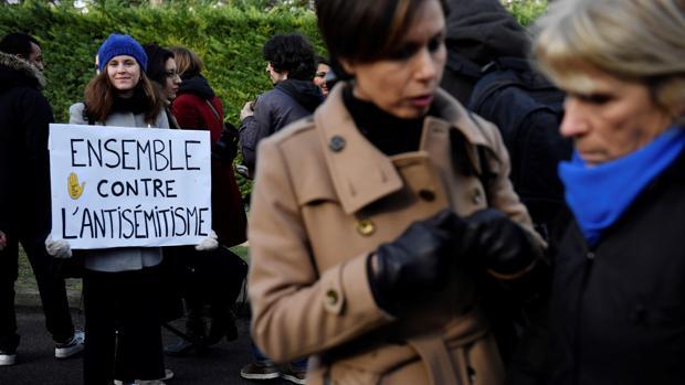 Una mujer sostiene un cartel contra el antisemitismo mientras un grupo de personas se reúne para participar en el homenaje celebrado en memoria de Ilan Halimi, un hombre judío que fue asesinado en 2006