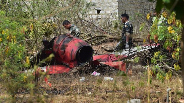 Dos militares observan el avión siniestrado tras chocar con otro aparato