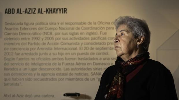 Fadwa Mahmour posa delante de la réplica de la cartera de su marido, Abd al Aziz al Khayyir, en la exposicóón «Decenas de miles«, que se puede ver en la Casa Árabe