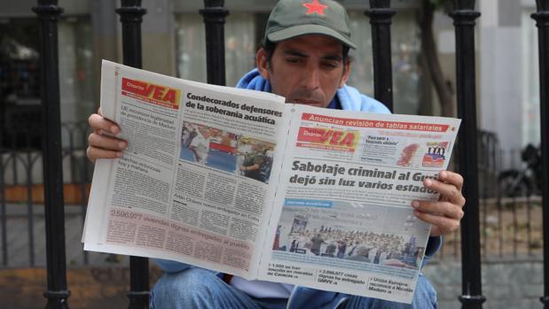 Un hombre lee un diario con titulares sobre el apagón eléctrico en Caracas (Venezuela)