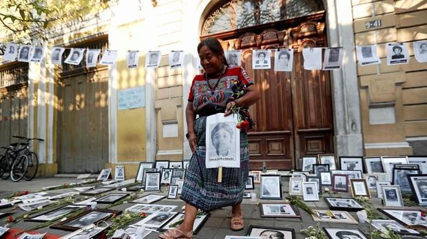 La activista indígena Rosalina, Tuyuc particpa, rodeada de fotografías de víctimas de la guerra civil, en una protesta frente al Congreso de Guatemala