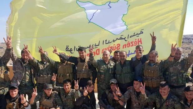 Combatientes de las Fuerzas Democráticas Sirias (FDS) hacen el signo de la victoria tras la caída de Baghouz
