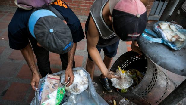 dos hombres mientras hurgan en una basura en busca de comida en una calle de Caracas en 2017