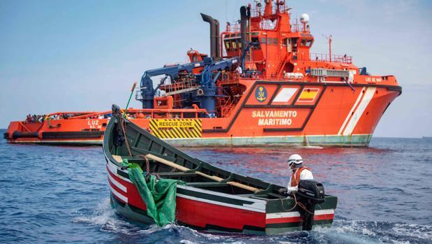 Un miembro de la agencia de búsqueda y rescate marítimo Salvamento Marítimo regresa a su embarcación a bordo de un bote utilizado por migrantes varados en el Estrecho de Gibraltar al final de una operación de rescate con la Guardia Civil Española