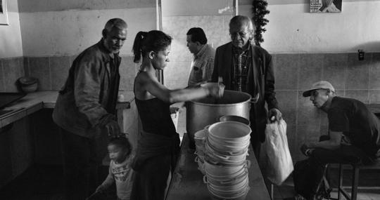 Una voluntaria sirve los platos de comida a los beneficiarios del comedor